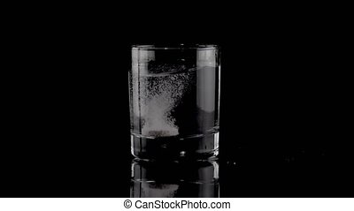 Effervescent tablet falling in a glass of water