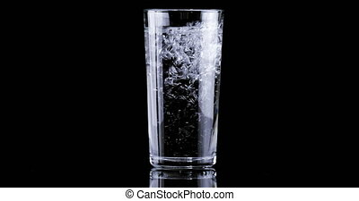 Effervescent tablet falling in full glass of water