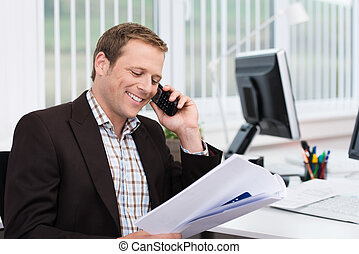 Efficient businessman answering a phone call at the office...