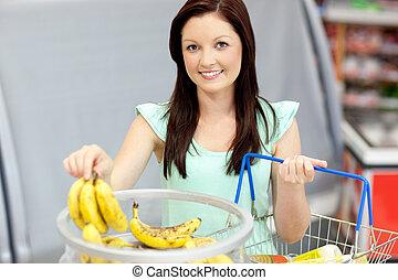 egészséges, mosolygós, élelmiszerbolt, shopping-basket, fényképezőgép, vásárlás, bolt, nő, banánok