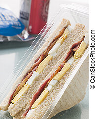 Egg And Bacon Sandwich On White Bread With A Bag Of Crisps ...