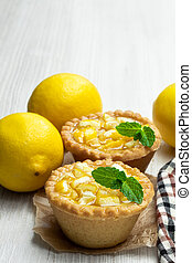 Egg custard tarts with jellied lemon on white wooden table