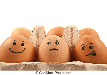 Close and low level capturing a group of brown eggs with painted faces arranged in carton with white background.