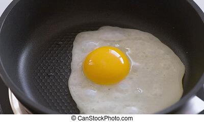 Egg fried on pan - Human hands puts egg on frying pan. Egg...