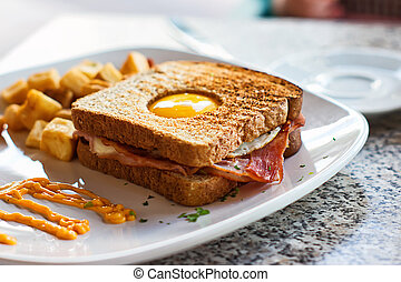 Egg in a Basket - Breakfast of egg, bacon, toast and hash...