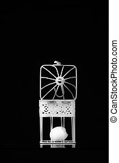 egg in a white cage on a black background