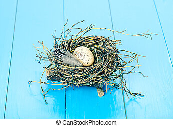 egg in nest on blue wooden background