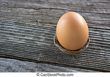 Egg in nest on wooden background