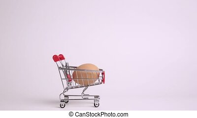 Egg in toy supermarket trolley on white background. Stop motion animation. Grocery shopping concept.