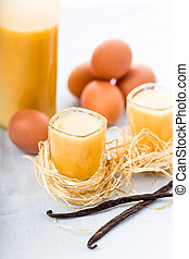 egg liqueur - Eggnog in glasses with fresh vanilla and eggs