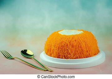 Egg thread cake (fios de ovos) topped with creamy coconut whipped cream