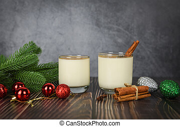 Eggnog delicious holiday drinks like themed parties with cinnamon pine cone and red ball for Traditional Christmas and winter holidays Homemade eggnog in glasses pine branch decorated