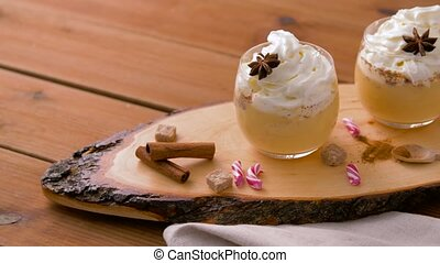 eggnog with whipped cream and spices on wood - christmas and...