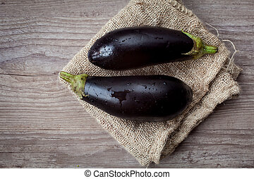Assortment of fresh eggplant on wooden background