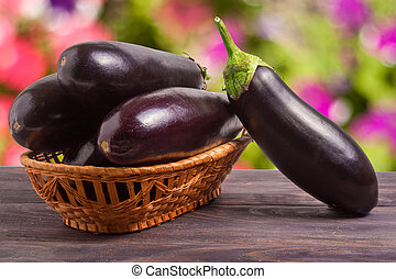 eggplant in a wicker basket on wooden table with blurred background