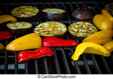 Eggplant slices, red and yellow peppers on grill rack