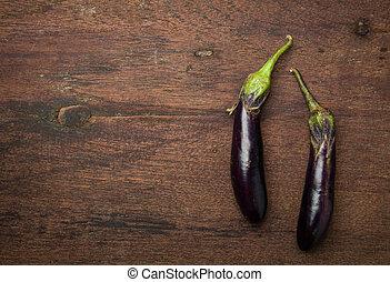 eggplants on wooden background.