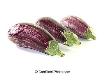 Eggplants - three fresh purple eggplant on a white...