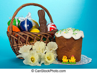 Eggs and a chocolate rabbit in a basket, an Easter cake,...