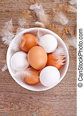 eggs and feathers on wooden table