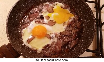 Eggs and meat in a frying pan
