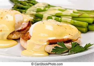Close up of two poached eggs, and canadian bacon, on an english muffin topped with hollandaise sauce with green asparagus on the side on white plate.