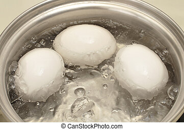 Eggs boiling - Closeup of three eggs boiling in pot of hot ...