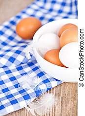 eggs in a bowl, towel and feathers on rustic wooden table