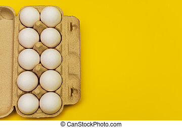 eggs in a cardboard box on a yellow background