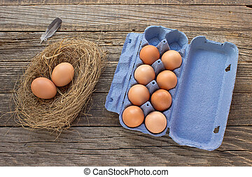 Eggs in nest and cardboard package on wooden background