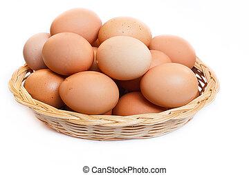Eggs in wicker basket.  - fresh raw brown eggs in a basket.