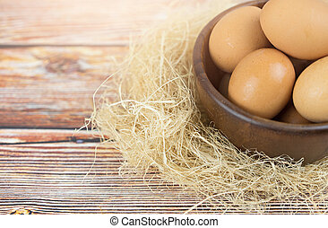 Eggs in wooden bowl on table. Food concept