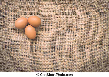 Eggs on old crumpled burlap, Background