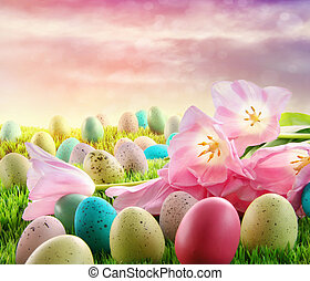 Eggs with pink tulips in the grass