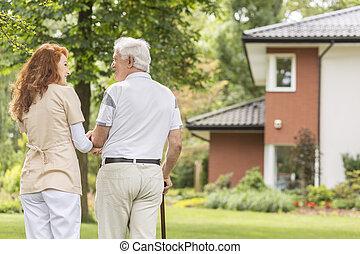 egy, hát, közül, egy, öregedő, gray-haired, ember, noha, egy, sétabot, és, övé, csörgőréce, házfelügyelő, jár, a kertben, képben látható, egy, napos, afternoon.