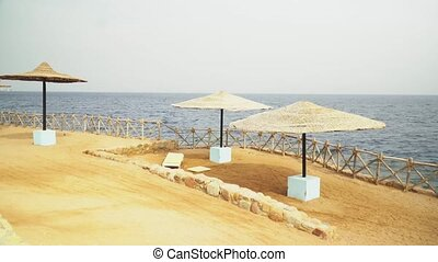 Egypt, Empty Sunny Beach with Umbrellas, Sun Beds on the Red Sea.