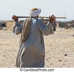 Traditional egyptian bedouin walking through a remote rural town