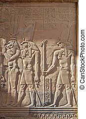 Egyptian engraved gods image on wall in Kom Ombo temple,...