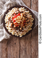 Egyptian kushari of rice, pasta, chickpeas and lentils Vertical top view