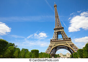 Eiffel Tower in Paris in a sunny day, blue sky and green trees