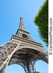 Eiffel Tower in Paris in a sunny summer day, clear blue sky and green tree