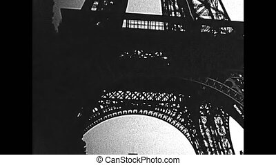 Paris Eiffel Tower, bottom view from Champ de Mars gardens. Historic restored BW archival footage on 1960 in Paris city of France.
