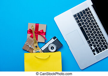 eiffel tower shaped toy, camera and gifts in shopping bag and cool laptop on the wonderful blue background