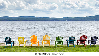 Eight colorful Adirondack chairs lined up on the beach ...