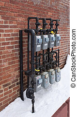 Gas Meters - Eight Gray Gas Meters in Snow with black pipes