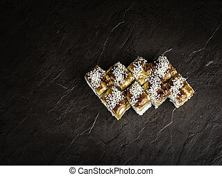 Eight rolls in Japanese style on a dark relief background top view