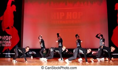 Eight teenagers boys and girls JUST BLACK team in glasses dance