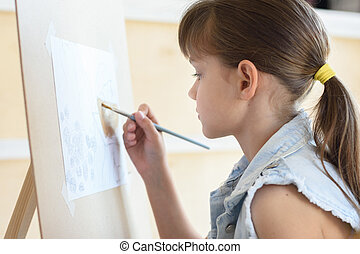 eight-year-old girl draws a brush pattern on an easel