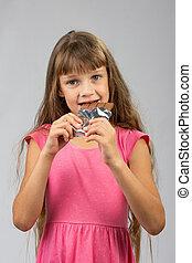 Eight-year-old girl eats chocolate bar
