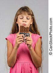 Eight-year-old girl with pleasure eats chocolate bar